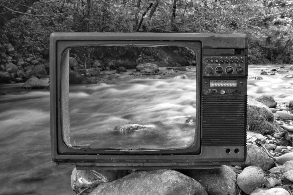 retro tv on river shore near forest